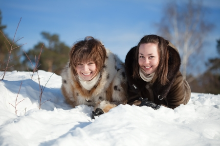 Happy girls lying down on the snow in winter photo
