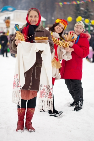 maslenitsa: Women in traditional  clothes with pancake during  Maslenitsa festival