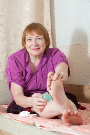Mature woman caring for the nails on your feet Stock Photo - 14024773