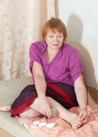 Mature woman caring for the nails on your feet photo