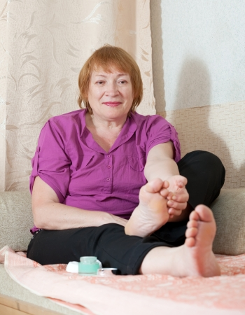 Mature woman looks at her toenails photo