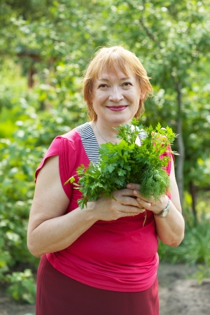 Mature woman with harvested dill and parsley  in garden photo