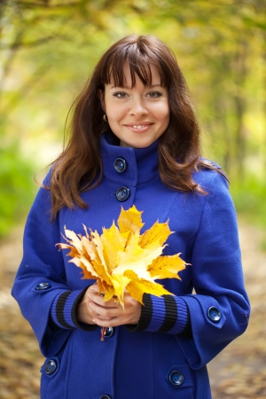 Outdoor portrait of   gilr with maple posy Stock Photo - 14024798