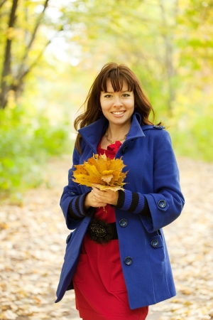 Outdoor portrait of   woman with maple posy Stock Photo - 14024795