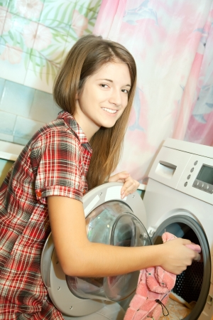 Teenager girl loading the washing machine at her home photo