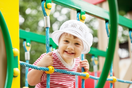 fun in the sun: Happy two-year child on slide playground area