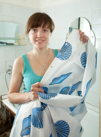 Young woman with shower curtain  in her bathroom photo
