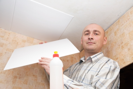 Man glues ceiling tile at home Stock Photo - 14103085