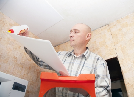 guy glues ceiling tile at home Stock Photo - 14103086