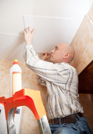 Man glues ceiling tile at home Stock Photo - 14109639