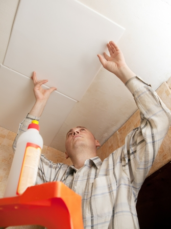 Man glues ceiling tile at home Stock Photo - 14103089