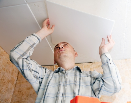 Man glues ceiling tile at home Stock Photo - 14109634