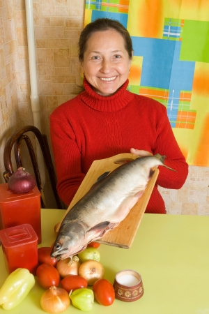 Woman with red fish in her kitchen photo