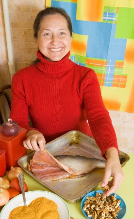 Mature woman is stuffing  fish by walnut photo