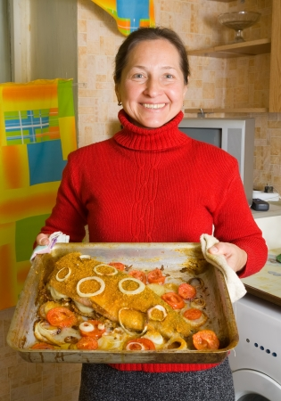 Mature woman with breaded fish in cook griddle photo