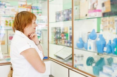 condones: Mujer madura cerca de mostrador en farmacia drugstor
