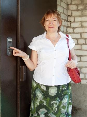 Mature woman pushing button of house intercom  photo