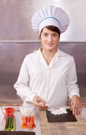 Cook woman making  japanese sushi rolls in kitchen photo