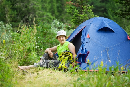Happy female hiker in front of camp tent against forest photo