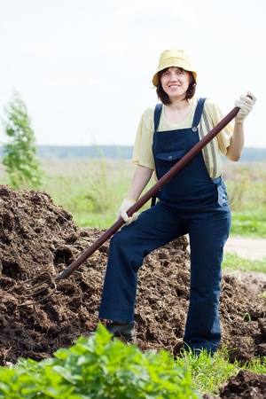 manure: Female farmer works with manure at field