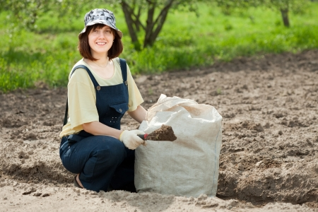 agriculturalist: woman fertilizes the soil in garden Stock Photo