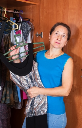 Mature woman chooses dress in wardrobe at her home photo