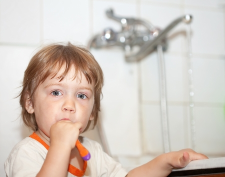 hygeine: Two-year baby gir brushing her teeth in bathroom