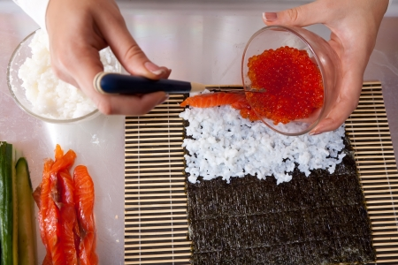 Closeup of cook making  Japanese sushi rolls  with salmon and caviar photo