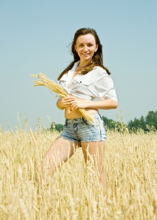 girl  with  wheat ear at  field in summer photo