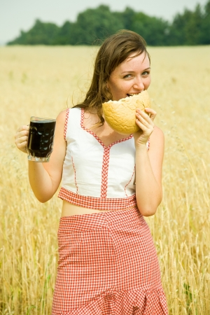 Girl  with quass and bread  at wheat field photo