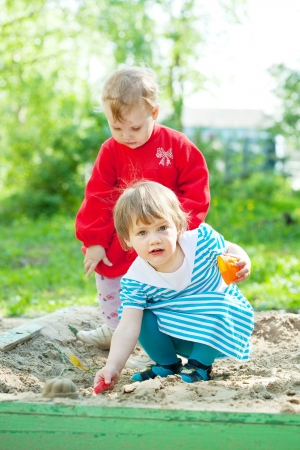 two children playing with sand in sandbox photo