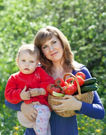 Happy woman and child with  harvested vegetables in garden photo