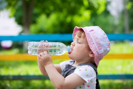 1 2 years:  two-year child drinks from plastic bottle in park
