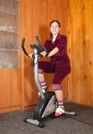 Young woman working out on exercycle at home photo