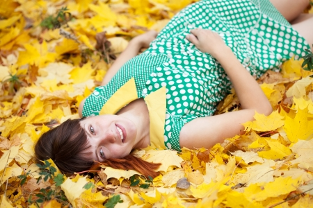lies down: Young woman lies in maple leaves at autumn park Stock Photo