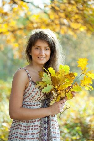 happy seasonable: Outdoor portrait of   girl with oak leaves posy