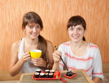 Two happy women eating sushi rolls photo