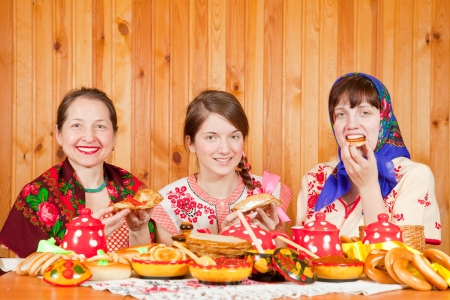 Women in traditional clothes celebrating Shrovetide and eats pancake  Stock Photo - 14368374