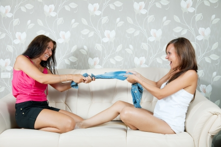 divide: Happy girls divide  clothes on sofa in livingroom at home Stock Photo