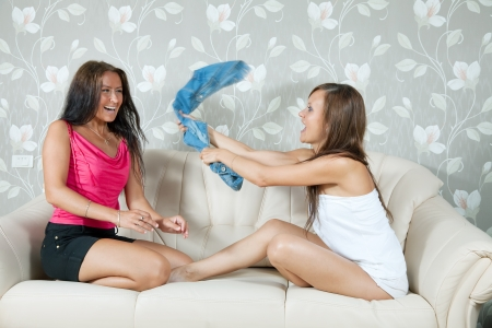Happy girls playing with clothes on sofa in livingroom at home photo
