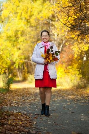 happy seasonable: walking mature woman in autumn park Stock Photo