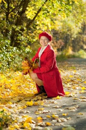Outdoor portrait of  happy mature woman with maple posy Stock Photo - 14397841