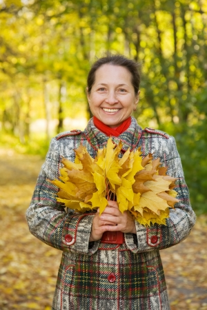 Portrait of   senior woman with maple leaves in autumn park photo