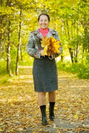 senior woman  in coat at autumn park photo