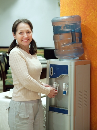 pours: Woman pours   water from water cooler  Stock Photo