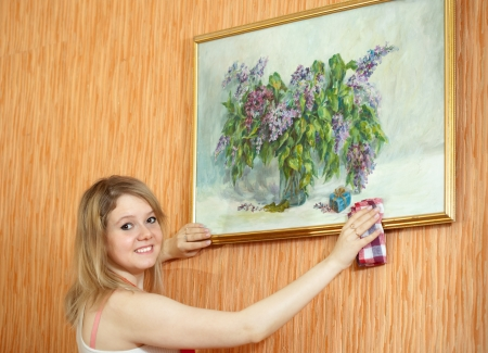 Young woman wipes the dust  on picture at home photo