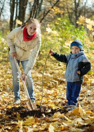 woman with  preschooler son setting tree in autumn garden photo