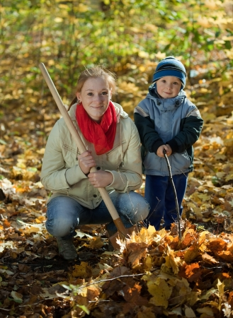 woman with her son working with spade in autumn photo