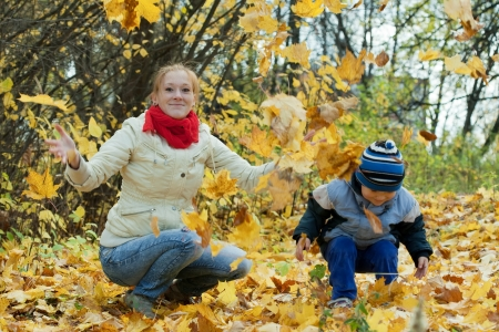 Happy mother with   boy throw up maple leaves in autumn Stock Photo - 14431966