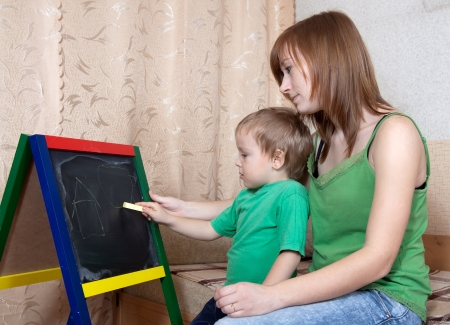 Mother and child draws on the blackboard with chalk photo
